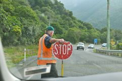 Worker hold Stop sign on highway Stock Photo