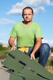 Worker holding  bitumen roof shingles on top of building Royalty Free Stock Photography