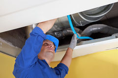 Worker holding blue pipe. In place under air ducts royalty free stock photos