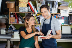 Worker Holding Book While Colleague Pointing At It. Portrait of happy male worker holding book while colleague pointing at it in factory Stock Photography