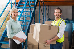 Worker holding box with manager holding clipboard. In a large warehouse Royalty Free Stock Photos