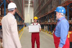Worker holding box in warehouse. Worker in uniform holding box, two others looking at him royalty free stock photography