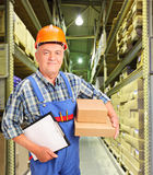 Worker holding boxes and clipboard at warehouse. A male worker in uniform holding boxes and clipboard at warehouse Stock Images