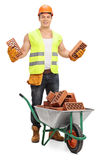 Worker holding bricks behind a wheelbarrow Royalty Free Stock Images