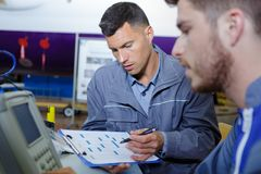 Worker holding clipboard while talking to colleague royalty free stock photography