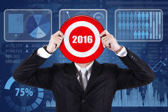 Worker holding dartboard in front of financial statistics Stock Image