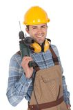 Worker holding drill and wearing hard hat Stock Images