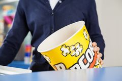 Worker Holding Empty Popcorn Tub At Cinema. Midsection of female worker holding empty popcorn tub at cinema concession stand stock photography