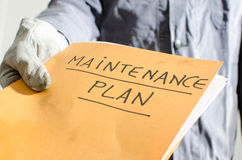 Worker holding a folder of maintenance plan Stock Images