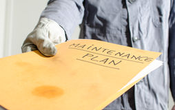 Worker holding a folder of maintenance plan Stock Image