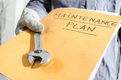 Worker holding a folder of maintenance plan and monkey wrench Royalty Free Stock Photography