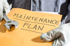 Worker holding a folder of maintenance plan and monkey wrench Stock Image