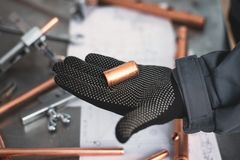 Pipework. Worker is holding in hands a brass pipe trimming on a fitter workbench background. Pipework stock image
