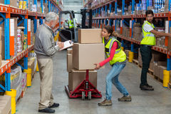 Worker is holding heavy cardboard boxes and looking her manager Stock Photography