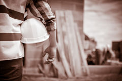 Worker holding a helmet with background of construction site. Stock Photography