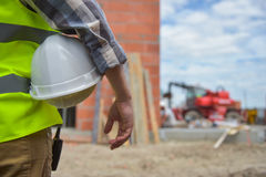 Worker holding a helmet with background of construction site. Stock Photos