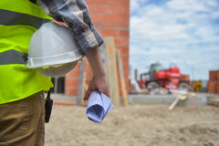 Worker holding a helmet with background of construction site. Royalty Free Stock Image