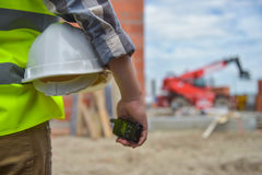 Worker holding a helmet with background of construction site. Stock Images