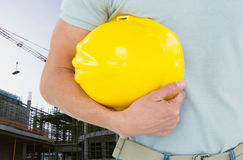 Worker holding his hard hat on the construction office. Digital composite of architect in construction  site Royalty Free Stock Images