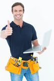 Worker holding laptop while gesturing thumbs up. Portrait of worker holding laptop while gesturing thumbs up over white background Royalty Free Stock Image