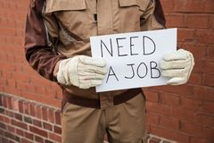 Worker holding placard with the text need a job Royalty Free Stock Images