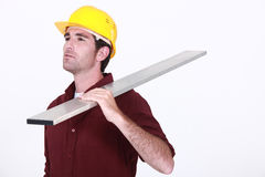Worker holding a plank. Stock Photos