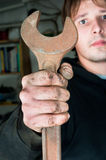 Worker holding spanner. Worker holding large open-end wrench stock images