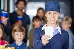 Worker Holding Tickets While Families Waiting In. Portrait of happy female worker holding tickets while families waiting in background at cinema royalty free stock photography