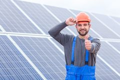 Worker holding on to hard hat and showing thumb up against background of solar panels stock photos