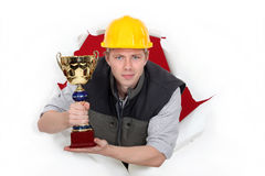 Worker holding a trophy cup. Royalty Free Stock Image