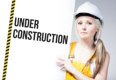 Worker holding under construction sign on information board Royalty Free Stock Images