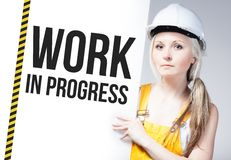 Worker holding work in progress sign on information board Stock Photos