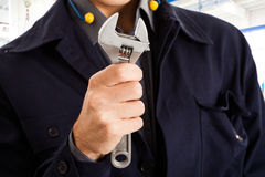 Worker holding a wrench Stock Images