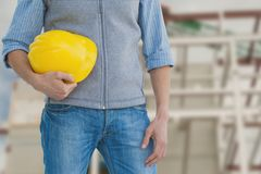 Worker holding a yellow helmet against construction royalty free stock photos