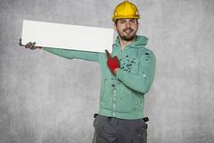 The worker holds a blank board, points to an empty space. Protective helmet on the head Royalty Free Stock Images