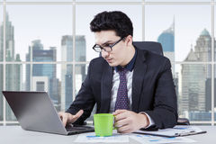 Worker holds coffee while typing on laptop Stock Photo