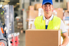 Worker holds package in warehouse of forwarding. Warehouseman with protective vest holds package, he standing at warehouse of freight forwarding company Stock Images