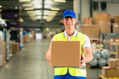 Worker holds package in warehouse of forwarding. Warehouseman with protective vest and scanner, scans bar-code of package, he standing at warehouse of freight Stock Photo