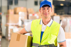 Worker holds package in warehouse of forwarding. Warehouseman with protective vest and scanner, holds package, he standing at warehouse of freight forwarding Royalty Free Stock Image
