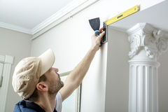 Worker holds putty knife and measures the wall corner using metal angle. Finishing work Royalty Free Stock Photos