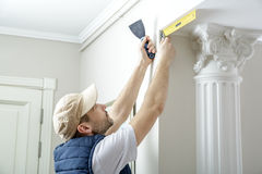 Worker holds putty knife and measures the wall corner using metal angle. Finishing work Stock Photo