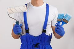 A worker holds a roller and paint brushes close-up on a white background. A worker in blue uniform and gloves holds a roller and paint brushes close-up on a Royalty Free Stock Image