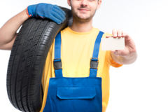 Worker holds tire and empty businesscard in hands Stock Photography