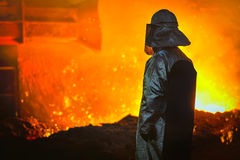 Worker with hot steel. In the factory Stock Photos
