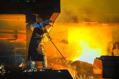 Worker with hot steel in the steel plant. Worker with hot steel Royalty Free Stock Image