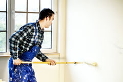 Worker house painter painted the walls in  white Royalty Free Stock Image