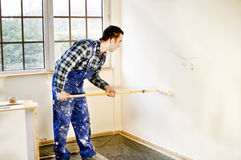 Worker house painter painted the walls in white Stock Photo