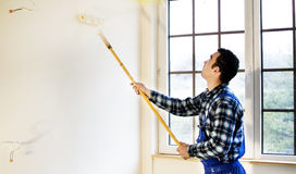 Worker house painter painted the walls in yellow Stock Photo