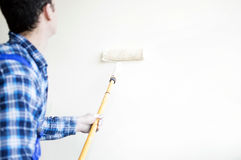 Worker house painter paints a wall Royalty Free Stock Photo