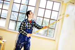 Worker house painter paints a wall Royalty Free Stock Images